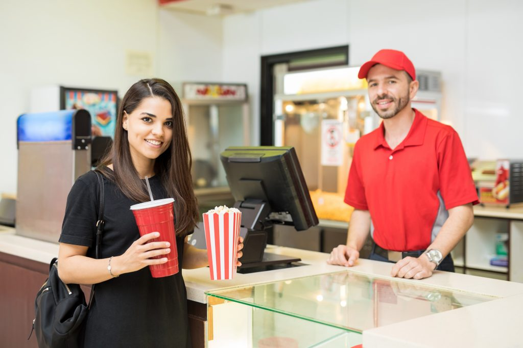 Service industry worker at a movie theater with customer.